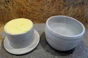 Große Butterdose in weiß. Nach dem Schrühbrand habe ich sie mit weißer Engobe besprichen und nochmals geschrüht. Danach erfolgte der Glasurbrand bei 1200 Grad. Glasur: Weiß glänzend. Nun wurden die gelben Punkte und der Schriftzug aufgebracht und nochmals bei 1200 Grad gebrannt. Die Maße: Unterteil Höhe: gut 7,5 cm / Durchmesser: 12 cm / Oberteil Höhe: 7 cm / Durchmesser am Deckel: 12,5 cm / Fassungsvermögen für die Butter: ca. 250 g / Preis: 34,90 Euro / Galerie-Nr:P10500383940. Hier, die beiden Teile nebeneinander. Auf den beiden folgenden Fotos, sehen Sie diese Butterdose in zwei weiteren Ansichten.